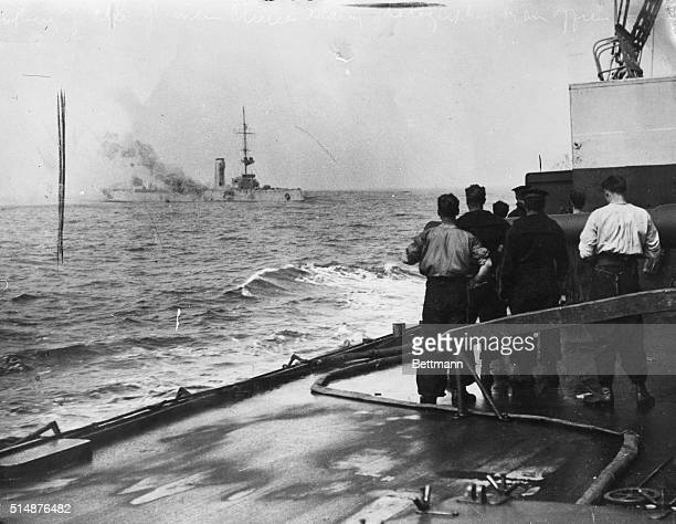 German Cruiser Mainz On Fire at the Battle of Heligoland British sailors watch from the deck of a battleship