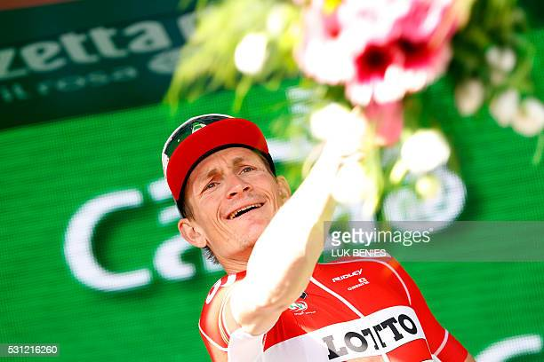 German cyclist Andre Greipel of Lotto Soudal team launches a bouquet of flowers as he celebrates on the podium after winning the 7th stage of 99th...