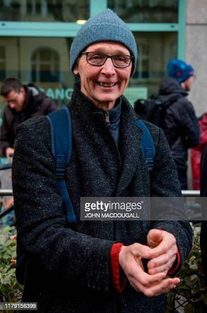 German dairy farmer Heiner Luetke applauds demonstrators in front of the Moabit administrative court in Berlin on October 31 2019 before appearing in...