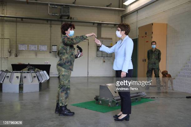 German Defence Minister Annegret Kramp-Karrenbauer examines a covid test vial offered by Doctor Schalke as a member of the Bundeswehr, the German...