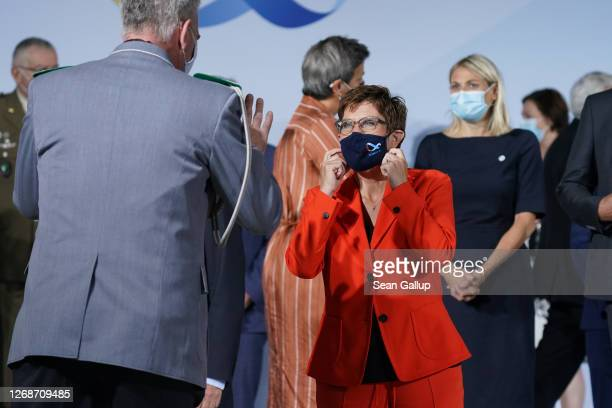 German Defence Minister AnnegretKramp Karrenbauer prepares to take off her face mask for a group photo at a meeting of European Union member states...