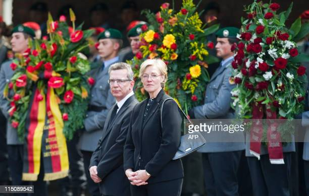 German Defence Minister Thomas de Maiziere and his wife Martina wait to see off the coffins of three German soldier killed in Afghanistan outside the...