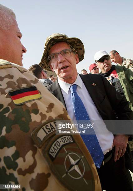 German Defence Minister Thomas de Maiziere talk to a soldier at PRT Kunduz on October 06 2013 in Kunduz Afghansitan Westerwelle and de Maiziere visit...