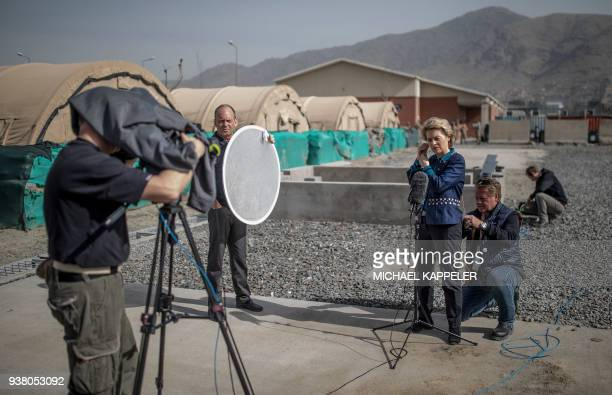 German Defence Minister Ursula von der Leyen is given an intercom headphone as she prepares for an TV statement at the airport in Kabul on March 26...
