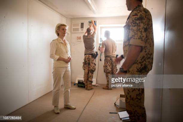 German defence minister Ursula von der Leyen looks on as an accommodation container for members of the German armed forces is set up at Camp Castor...