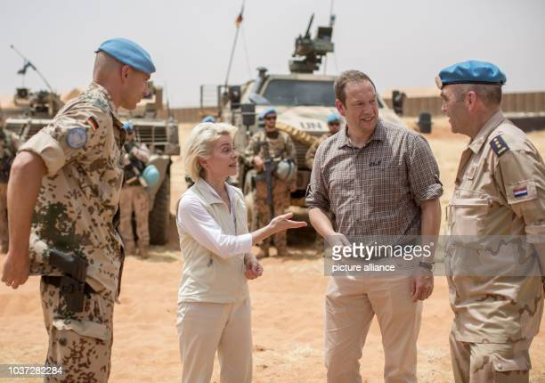 German defence minister Ursula von der Leyen talks to Henning Otte , member of the German Bundestag parliamentary defence committee, Marc Vogt , a...