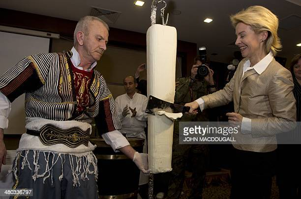 German Defence Minister Ursula von der Leyen tries her hand at slicing a Turkish regional specialty ice cream made with goat milk during a reception...