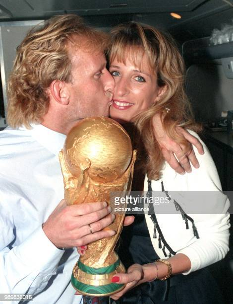 German defender Andreas Brehme holds the World Cup trophy in his hand while he kisses his wife Pilar on their return trip to Frankfurt Main after...