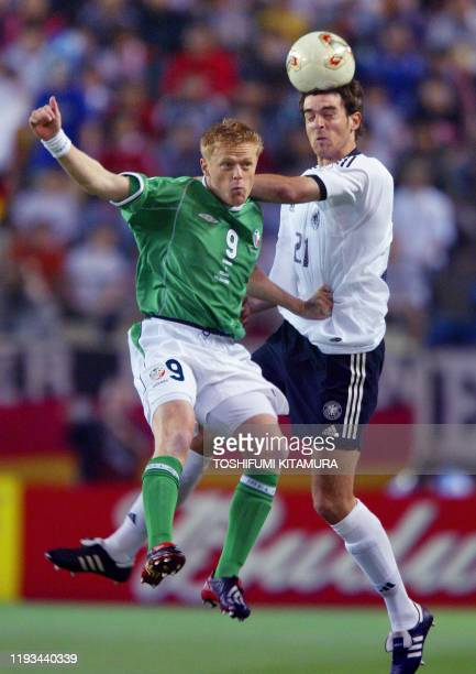 German defender Christoph Metzelder heads the ball in front of Irish forward Damien Duff during the Group E first round match Germany/Ireland of the...