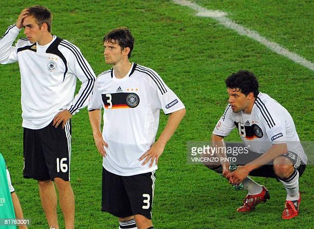 German defender Philipp Lahm German defender Arne Friedrich and German midfielder Michael Ballack react after Spain won the Euro 2008 championships...