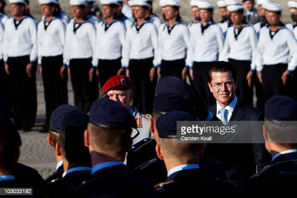 German Defense Minister KarlTheodor zu Guttenberg walks in front of soldiers at a swearingin ceremony for new recruits in front of the Reichstag the...