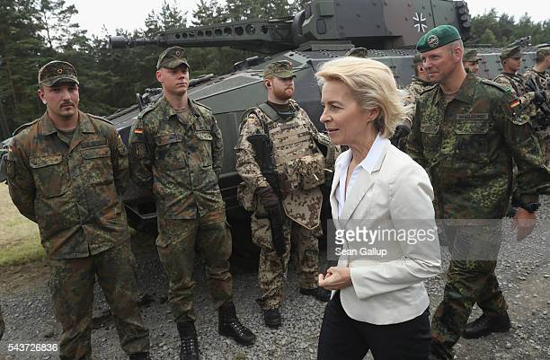 German Defense Minister Ursula von der Leyen chats with soldiers of the Bundeswehr the German armed forces following a demonstration of capabilities...
