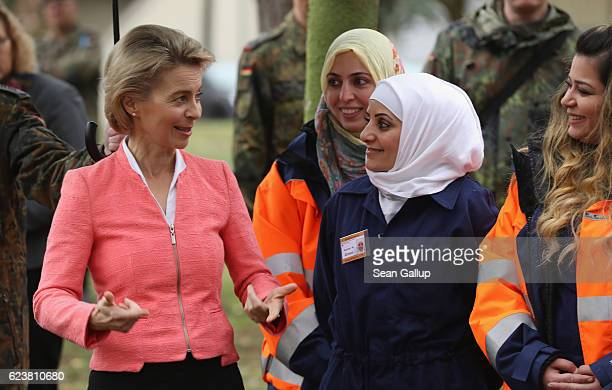 German Defense Minister Ursula von der Leyen chats with Syrian refugees including Syrian Kurdish refugee Nesrin Ahmad during a demonstration of a...
