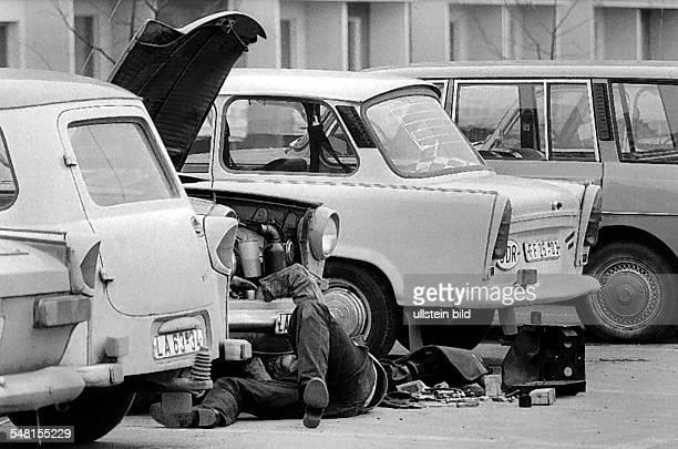 German Democratic Republic Bezirk Erfurt Erfurt man is reparing his Trabant car on the street