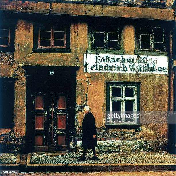 German Democratic Republic Bezirk Magdeburg Osterwieck - old woman is passing a rotten house - um 1979