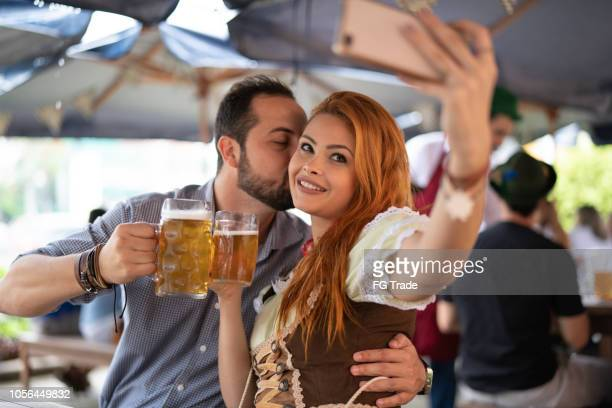 german descent couple taking a selfie at happy hour in blumeanu, santa catarina, brazil - northern european descent stock pictures, royalty-free photos & images
