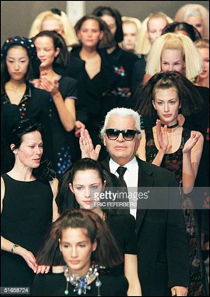German designer Karl Lagerfeld acknowledges applause 12 March as he walks down the runway with his models at the end of Chanel's 1997/98 Fall/Winter...