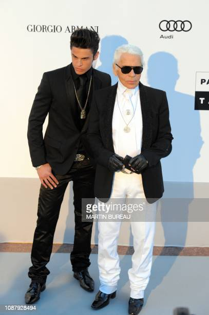German designer Karl Lagerfeld and French model Baptiste Giabiconi pose while arriving to attend the 2010 amfAR's Cinema Against Aids on May 20 2010...