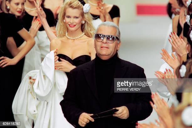 German designer Karl Lagerfeld flanked by German model Claudia Schiffer acknowledges the audience at the end of the presentation of Chanel's...