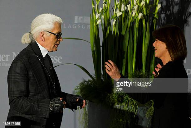 German designer Karl Lagerfeld gives to Princess Caroline of Monaco the charity Award of the association People in Europe on December 12 2011 in...