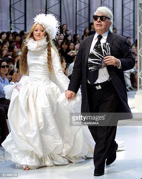 German designer Karl Lagerfeld of Chanel leads Japanese model Devon Aoki wearing a wedding dress during the autumn/winter 20002001 Chanel collection...
