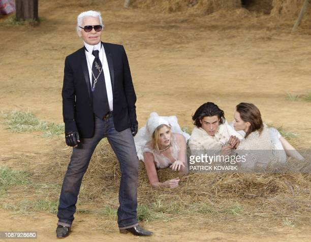 German designer Karl Lagerfeld poses next to Dutch model Lara Stone French model Baptiste Giabiconi and Danish model Freja Beha Erichsen at the end...
