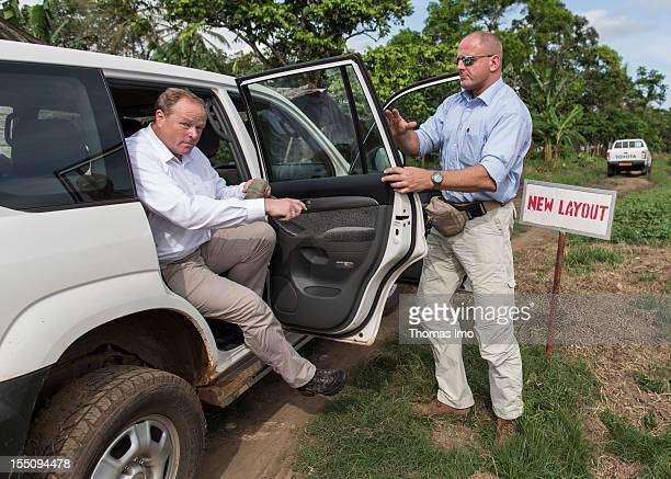 German Development Minister Dirk Niebel exits a car while a BKA security agent opens the door on a cocoa plantation on October 30 2012 in Mondoni...