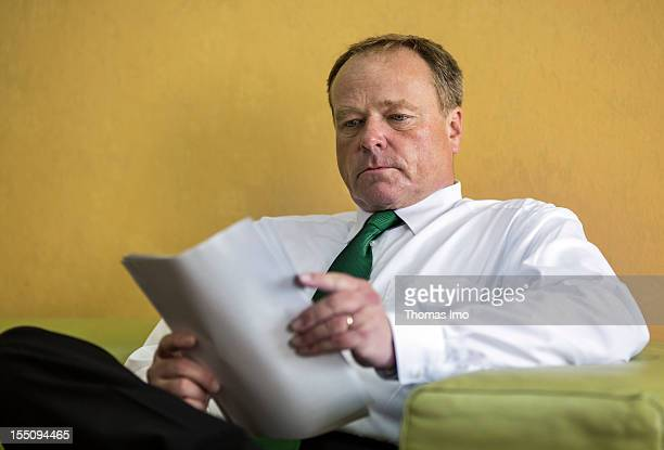 German Development Minister Dirk Niebel reads his files at the airport on October 30 2012 in Yaounde Cameroon Niebel's visit to Cameroon will focus...