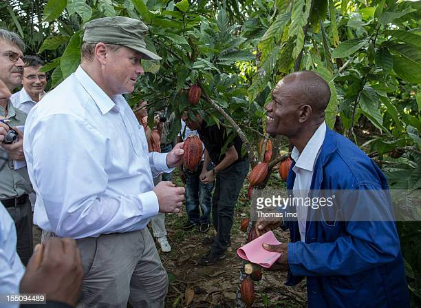 German Development Minister Dirk Niebel talkes to Ojong James a cocoa farmer after he cut a cocoa fruit from a tree while he visits a cocoa...
