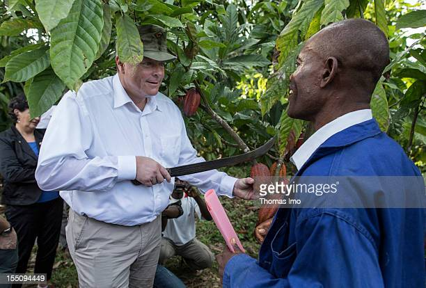 German Development Minister Dirk Niebel uses a machete to cut a cocoa fruit from a tree and speaks to Ojong James a cocoa farmer during his visit to...