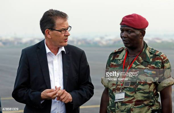 German Development Minister Gerd Mueller arrives at the airport of Bangui on March 13 2014 Mueller talks with a security officer about the situation...
