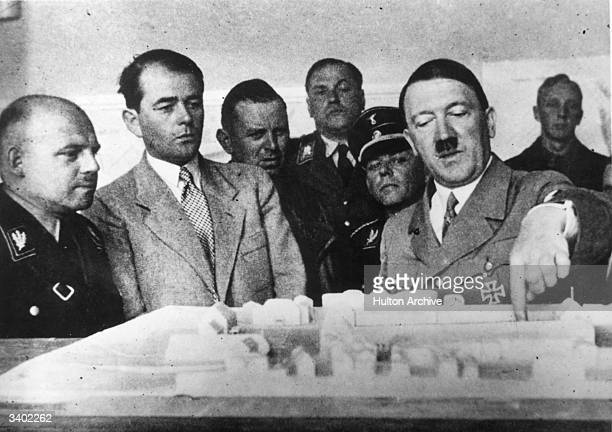 German dictator Adolf Hitler discussing plans for a new administration building for the provincial government in Weimar GermanySecond from the left...