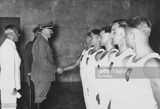 German dictator Adolf Hitler shakes hands with British rower Jack Beresford after he and Leslie Frank 'Dick' Southwood won the double sculls event at...