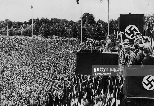 German dictator Adolf Hitler speaking to a crowd of uniformed men from a box on a raised platform adorned with swastikas and German flags at a Nazi...