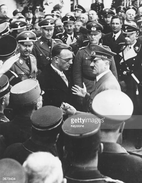 German dictator Adolf Hitler talks to Dr Artur von Seyss-Inquart, the last Chancellor of Austria, after Hitler's speech in the Heldenplatz, Vienna,...