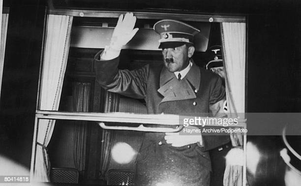 German dictator Adolf Hitler waves from his bulletproof railway carriage as he leaves Florence for Berlin after a visit to Italian leader Benito...