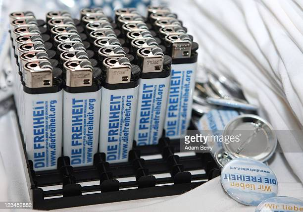 German Die Freiheit Party cigarette lighters and button sit on sale outside a rally by the party on September 3 2011 in Berlin Germany The Freiheit...