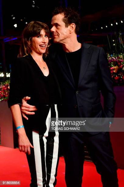 German director and president of the jury Tom Tykwer poses with his partner Marie Steinmann on the red carpet upon their arrival at the Berlinale...