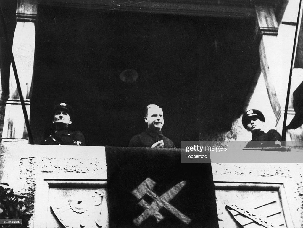 Dissidente alemão ex-membro do Partido Nacional-Socialista, Otto Strasser (1897 - 1974) dirigindo-se a membros de seu partido rival, a Frente Negra, de uma varanda pendurada com a bandeira de espada e martelo do partido, por volta de 1932. Imagem: Getty Images