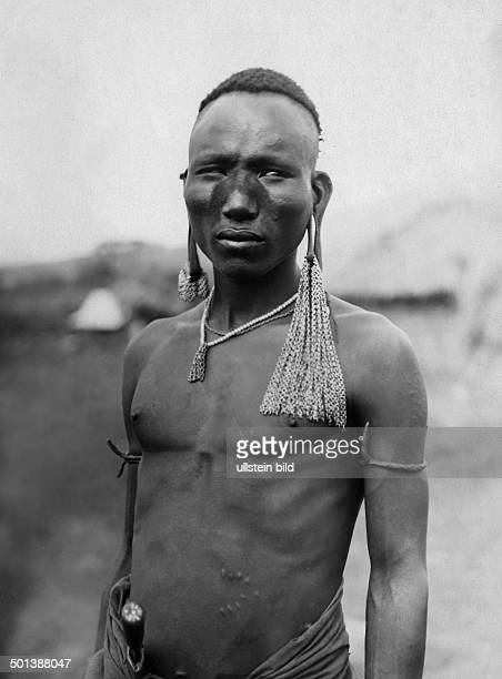German East Africa portrait of a native probably of the Maasai people with ornamental scars and earlobes prolonged by earrings probably in the 1910s