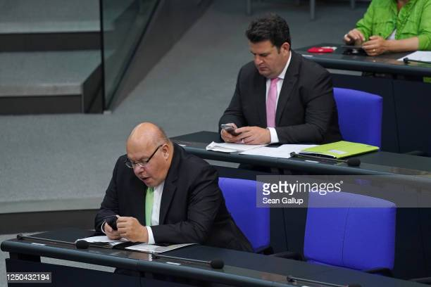 German Economy and Energy Minister Peter Altmaier and Minister of Work and Social Affairs Hubertus Heil use smartphones during debates at the...