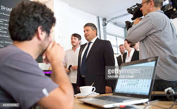 German Economy Minister and Vice Chancellor Sigmar Gabriel passes by a man working at his notebook during his visit to BetaHouse a center which...