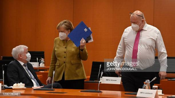 German Economy Minister Peter Altmaier looks on as German Chancellor Angela Merkel talks with German Interior Minister Horst Seehofer as she arrives...