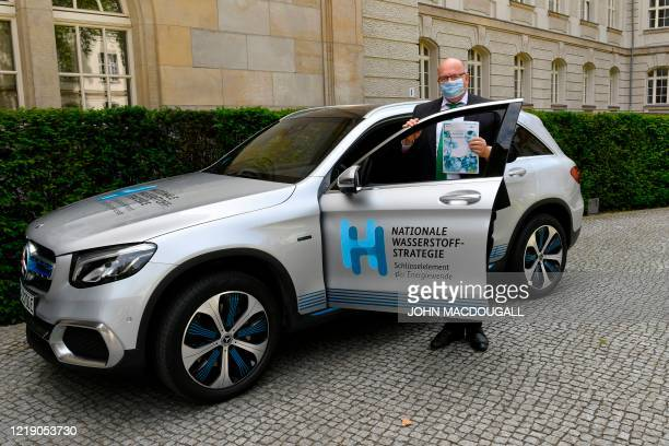 German Economy Minister Peter Altmaier wears a face mask as he poses next to a car to present the German government's hydrogen strategy on June 10...