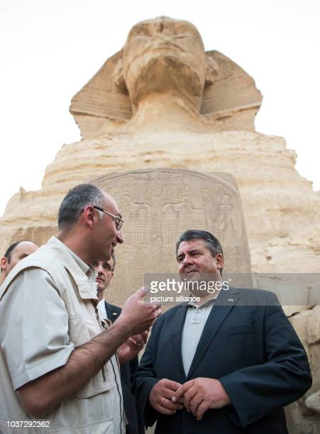 German economy minister Sigmar Gabriel talks to Tarek Tawfiq director of the Grand Egyptian Museum in Cairo during a visit to the Pyramids of Giza...