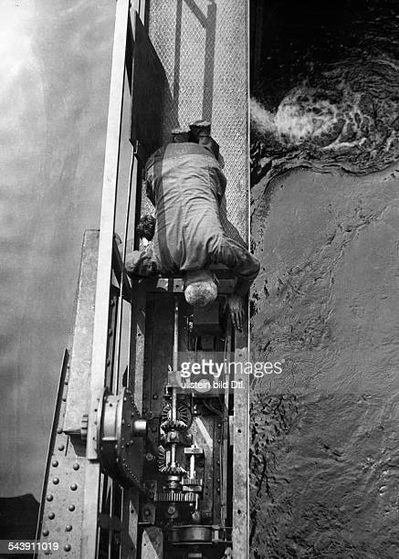German Empire Free State Prussia Berlin: Lock at the 'Muehlendamm', a man lubricating the gear of the lock - Photographer: Curt Ullmann- Published...