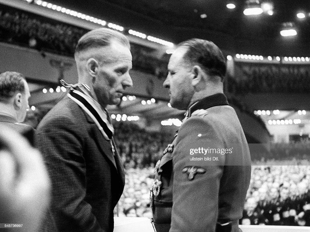 German Empire Free State Prussia Brandenburg Province Berlin: Big rally in the Berlin Sports Palace, awarding of the Knight's Cross of war merit to representatives of arm industry: SS-Obergruppenfuehrer Joseph (Sepp) Dietrich in conversation with the : News Photo