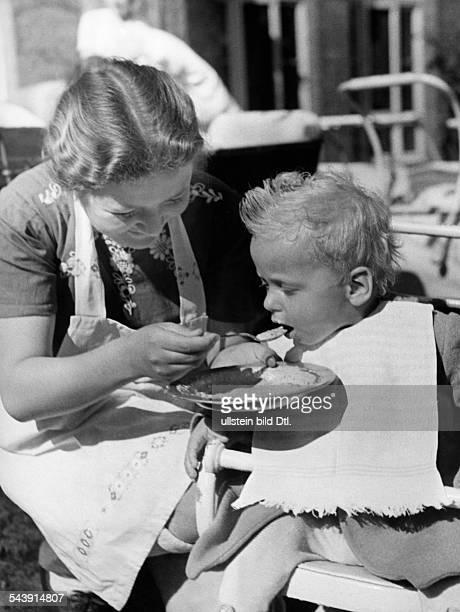 German Empire Free State Prussia Brandenburg Province in the German residential school in Hermannswerder near Potsdam a nursery nurse feeding a child...