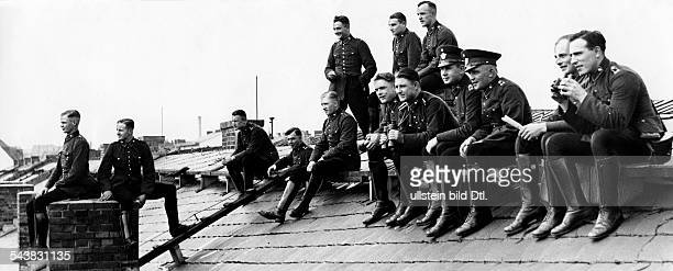 German Empire Free State Prussia Brandenburg Provinz Berlin Policemen watching a boxing fight in the Polizeistadion sitting on the roof of the casern...