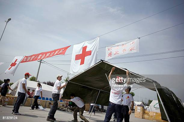 German engineers and their Chinese counterparts build a reception tent at the German Red Cross Field Hospital on June 2, 2008 in Dujiangyan, Sichuan...